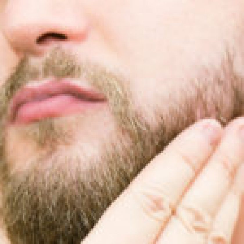 Brushing beard with hand after trimming